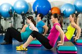 Fitness people in gym on step board; strengthening the abdominal muscles
