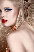 beautiful blond with hair in upstyle wearing dark fashion eyeshadow and red lips looking over should