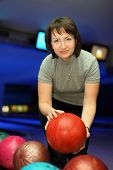 Woman takes  ball for playing in bowling and smiles