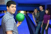 One fellow stands sideways and holds ball for playing in bowling and three friends hearten him, focu