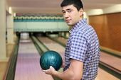 Young man stands sideways and and holds  ball for bowling