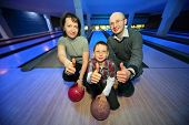Family of squatting in bowling club and shows  hands of ok, focus on  boy