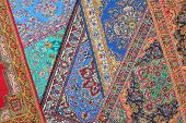 Seven varicolored carpets lie in random order on each other