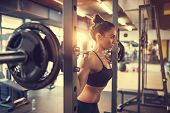 Fit beautiful girl doing squats with barbell in gym poster