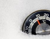Round thermometer with Celsius scale placed in a snow showing high temperature — warm winter weath poster