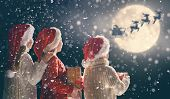 Merry Christmas and happy holidays! Cute little children with xmas presents. Santa Claus flying in h poster