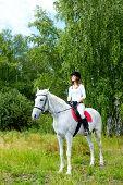 Image of happy female jockey sitting on appaloosa horse outdoors