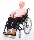 Happy elderly paraplegic woman sitting in a wheelchair on a white.