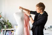 people, clothing and tailoring concept - fashion designer with dummy, cloth and pins making new dres poster
