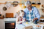 Family Is Cooking In Cozy Home Kitchen. Grandmother And Child Are Using Oven. Retired Woman And Litt poster