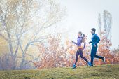 Woman and man jogging or running in park during autumn on a hill poster