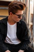 Young Modern Hipster Man In Sunglasses With A Fashionable Hairstyle In An Elegant Black Shirt In A W poster