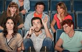 stock photo of bleachers  - Loud bearded man on phone annoys the audience in theater - JPG