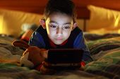 stock photo of preteen  - kid in bed wih videogame console on night - JPG