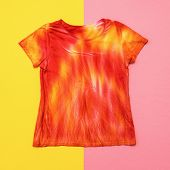 T-shirt In Bright Colors In Tie Dye Style On Yellow And Pink Background. Flat Lay. Staining Fabric I poster