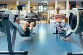 Front view of young Caucasian male and female athlete exercising with rowing machine in fitness stud poster