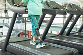 Low section of disabled active senior Caucasian woman with leg amputee exercising on treadmill in fi poster