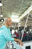 Side view of thoughtful active senior Caucasian woman leaning on railing in fitness studio. Strong a poster