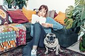Young Woman Reading A Book In His Home With Her Pet - Chill Out Concept - Singles Life Concept poster