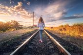 Standing Young Woman On The Railroad At Sunset In Summer. Slim Girl On The Railway Station. Rural In poster