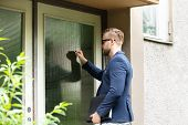 Man Standing At The Entrance Of The House Knocking The Door poster