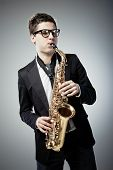 image of sax  - Young man playing sax on gray background - JPG
