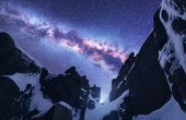 Milky Way And Snowy Mountains. Space. Beautiful Nature. Snow Covered Rocks And Starry Sky At Night.  poster