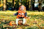 Cheerful Little Baby Boy In Halloween Costume Sitting On Pumpkin, Celebration poster