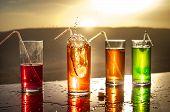 Cooling Summer Drink Concept. Cocktail Glasses Splashing On Sunset. Close Up Wet Glass Of Cold Drink poster