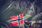 Trollstigen Mountain Road Landscape In Norway, Europe. Norwegian Flag Waving And Many Tourists Peopl poster
