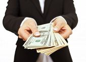picture of bribery  - Business executive in formal suit giving money as a bribe - JPG