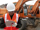 picture of heavy equipment operator  - road construction worker and heavy equipment on the background - JPG
