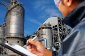 stock photo of refinery  - engineer oil refinery write on the notes book looking large oil refinery focus on refinery - JPG