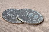 Two 500 japanese Yen coins on oriental beige fabric as background
