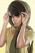 Portrait of an African American woman holding sunglasses with a stole over her head