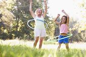 stock photo of hula hoop  - Grandmother and granddaughter hoola hooping together - JPG