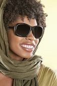 Happy African American wearing sunglasses with stole over her head