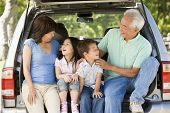 Grandparents With Grandkids In Tailgate Of Car