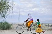 Masai women biking and walking through the savanna
