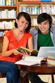Studenten - junge Frau und Mann in der Bibliothek mit Laptop und Buch lernen, sie sind einer Lerngruppe