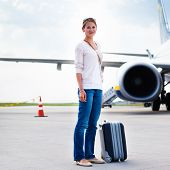 Just arrived: young woman at an airport having just left the aircraft