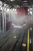 Vehicle on conveyor belt moving through car wash process