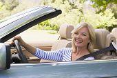 Mulher em carro conversível sorrindo