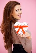 Vivacious beautiful brunette woman with a heart shaped Valentine gift looking seductively back at the camera over her shoulder