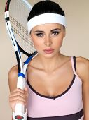 Beautiful female tennis player wearing a headband holding her racquet over her shoulder