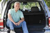 Man Sitting In Back Of Van Smiling