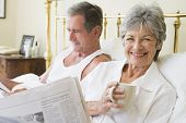 Couples In Bedroom With Coffee And Newspapers Smiling