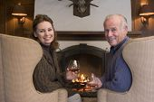 Couples Sitting In Living Room By Fireplace With Drinks Smiling