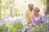 Couples Sitting Outdoors With Flowers Smiling