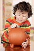 stock photo of thrift store  - Little boy with his a big piggybank in house - JPG